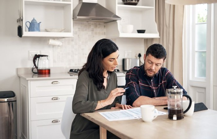 A man and woman sitting in their kitchen and talking while looking over papers.